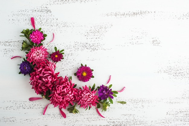 Flores de crisântemo vermelho na superfície de madeira branca