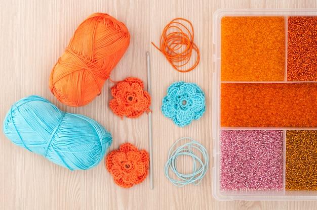 Flores de crochê de malha artesanal e caixa com miçangas para criar jóias feitas à mão em uma mesa de madeira. vista do topo