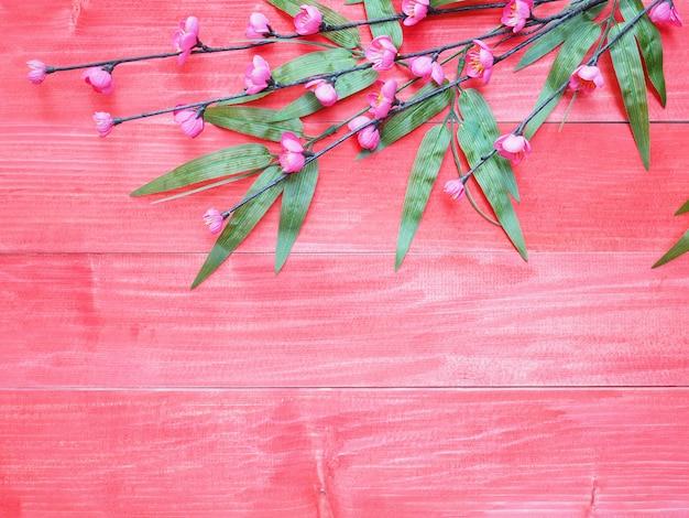 Flores de flor-de-rosa e folhas de bambu verde sobre fundo vermelho de madeira