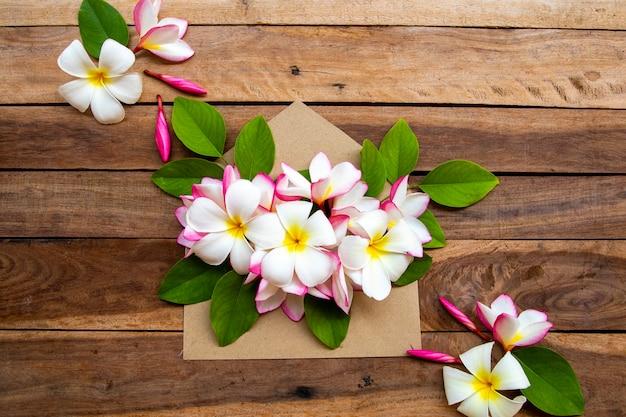 Flores de frangipani em envelope na superfície de madeira