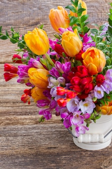 Flores de frésia azul, violeta e vermelha e tulipa laranja de perto