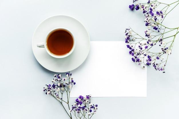 Flores de gipsófila em um fundo azul e uma folha branca em branco para escrever, espaço para texto