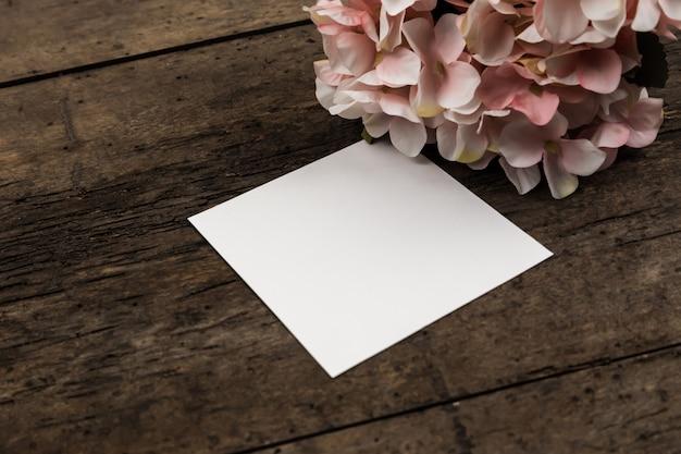 Flores de hortênsia rosa pastel e um pedaço de papel na madeira. copyspace para texto
