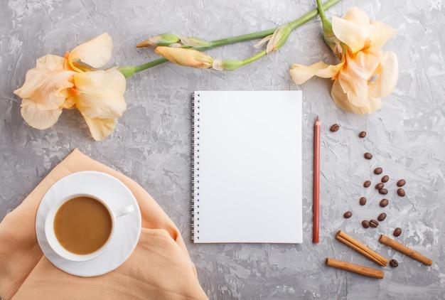 Flores de íris laranja e uma xícara de café com notebook em concreto cinza
