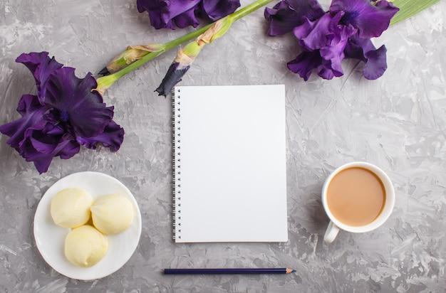 Flores de íris roxas e uma xícara de café com marshmallow e notebook em concreto cinza