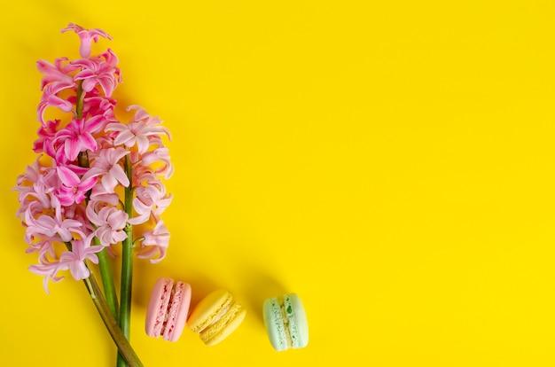 Flores de jacinto-de-rosa e macarons ou macaroons em amarelo