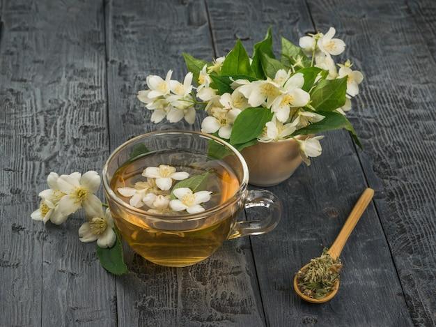 Flores de jasmim e chá de flores em uma tigela de vidro sobre uma mesa de madeira. uma bebida revigorante que faz bem à saúde.