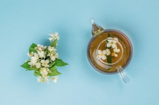 Flores de jasmim e um bule com chá de jasmim em um fundo azul.