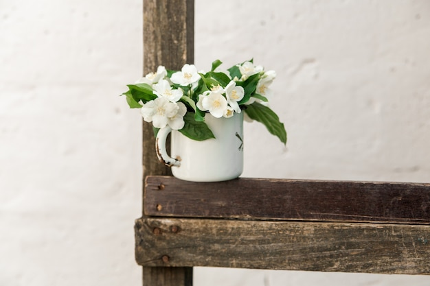 Flores de jasmim em taça de metal rústica.