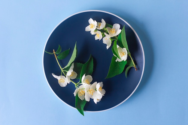 Flores de jasmim em um prato azul