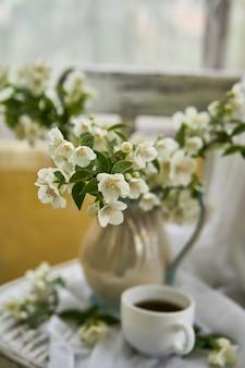 Flores de jasmim em um vaso branco. stillife com jasmim e café.