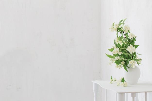 Flores de jasmim em um vaso na parede velha de fundo