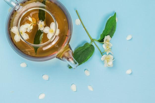 Flores de jasmim produzidas em um bule em um fundo azul. uma bebida revigorante que faz bem à saúde.