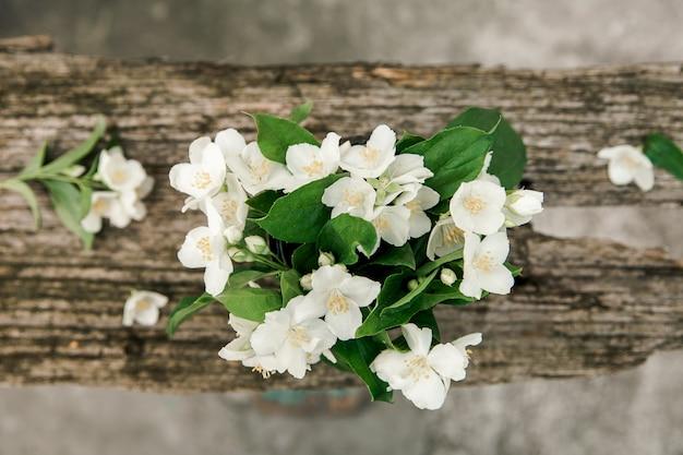 Flores de jasmim rústicas na madeira velha. vista do topo