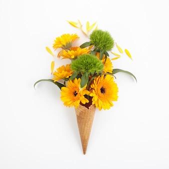 Flores de laranja e verdes em waffles de sorvete. vista superior, plana
