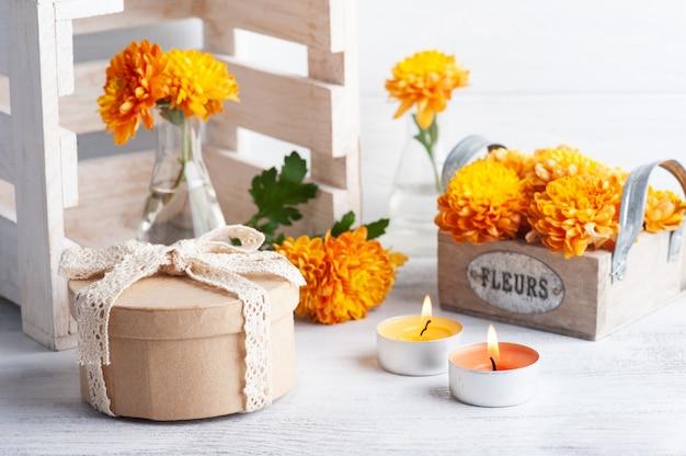 Flores de laranja em pote de vidro na mesa rústica. cartão comemorativo com velas acesas e caixa de presente kraft com sinal em francês flores