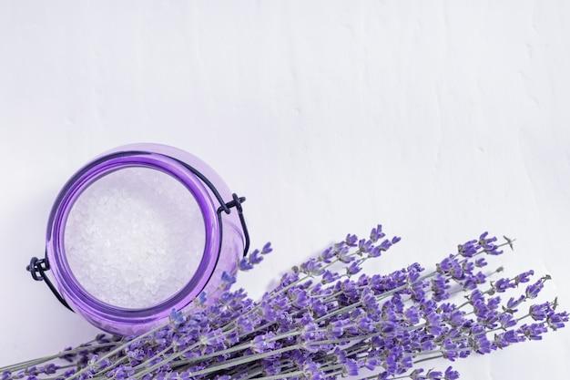 Flores de lavanda e jarra de vidro com sal marinho. conceito de spa. foco seletivo.