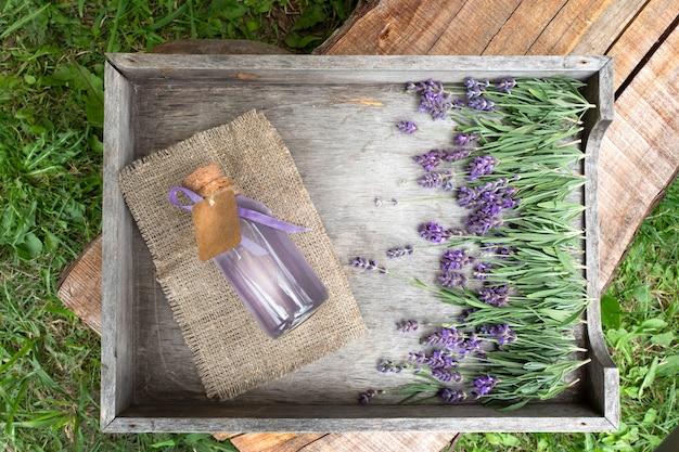 Flores de lavanda e óleo em uma caixa de madeira texturizada