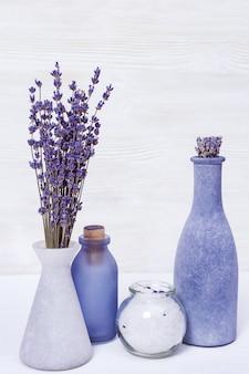 Flores de lavanda e sal marinho para procedimentos cosméticos, fundo de madeira, tema spa, espaço de cópia.