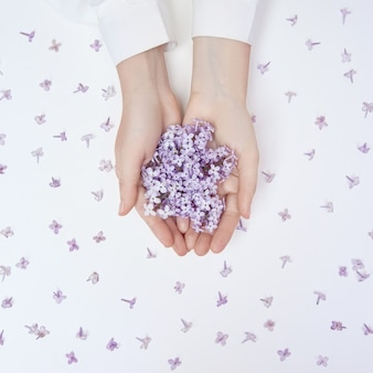Flores de lírio da primavera nas mãos de uma mulher deitada sobre uma mesa branca. cosméticos naturais para mãos, mãos anti-rugas. beleza natural de uma mulher