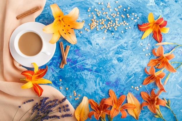 Flores de lírio-dia e lavanda laranja e uma xícara de café sobre um fundo azul de concreto