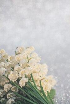 Flores de lírio do vale fecham com foco seletivo em fundo cinza claro. a beleza do conceito de natureza. cartão com espaço de cópia.