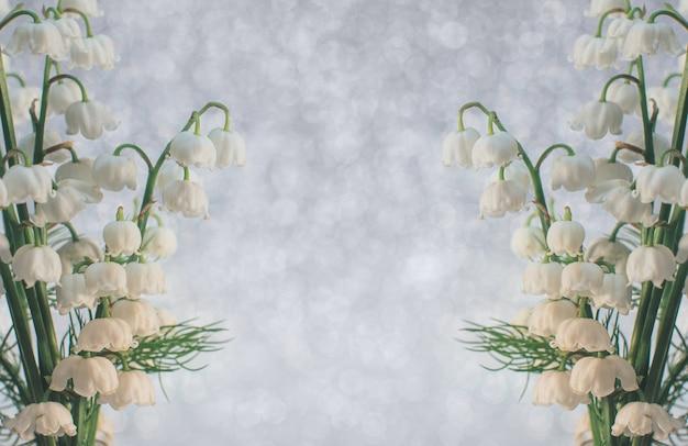 Flores de lírio do vale fecham-se com foco seletivo em um fundo cinza claro, a beleza de