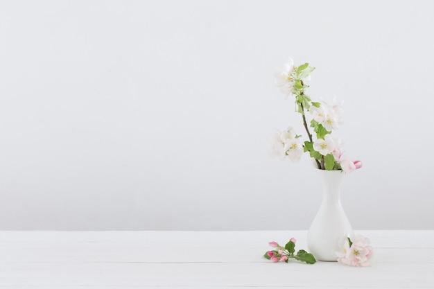 Flores de maçã em um vaso no interior branco