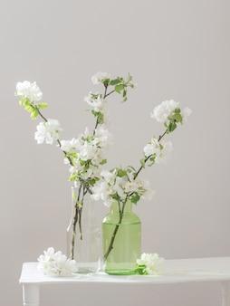 Flores de maçã em vaso de vidro com interior branco