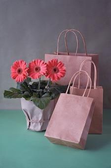 Flores de margarida do gerbera coral e ofício papper sacolas em papel verde