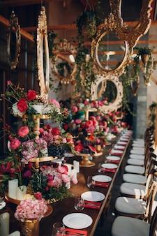 Flores de mesa de casamento com decoração de frutos e bagas nas cores verdes rosa brancas vermelhas.