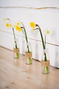 Flores de narciso em um vaso com água estão no chão no interior.