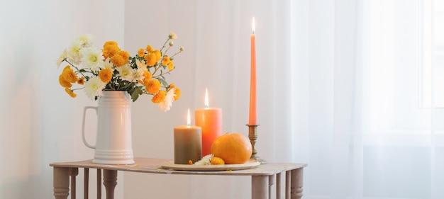 Flores de outono com velas acesas e abóboras na prateleira de madeira vintage