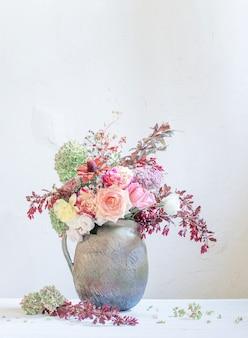 Flores de outono e frutas em jarro de cerâmica rústica na parede branca de fundo