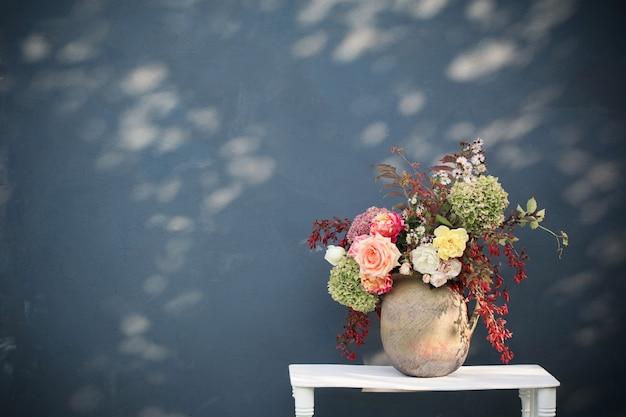 Flores de outono e frutas em um jarro de cerâmica rústico na parede azul de fundo