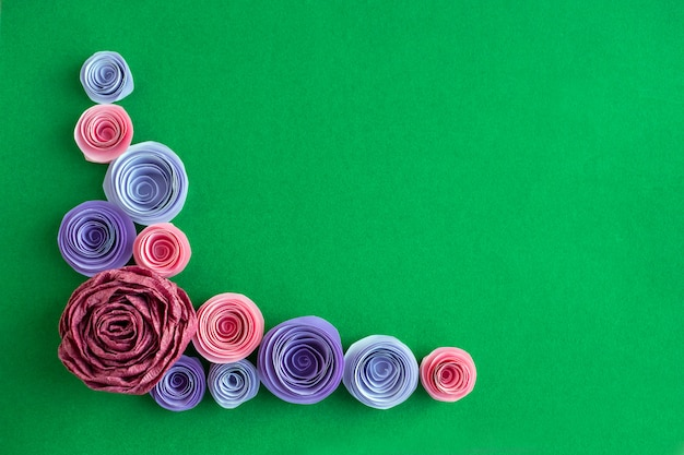 Flores de papel artesanal em ângulo de quadro sobre um fundo verde