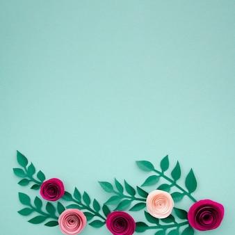 Flores de papel bonito e folhas no fundo azul