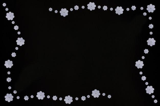 Flores de papel branco em fundo preto estilo plano com arte em papel espaço de cópia