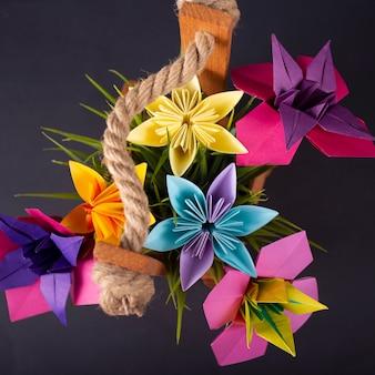 Flores de papel colorido artesanal origami buquê papel artesanato arte em uma cesta com grama no estúdio em blackbackground