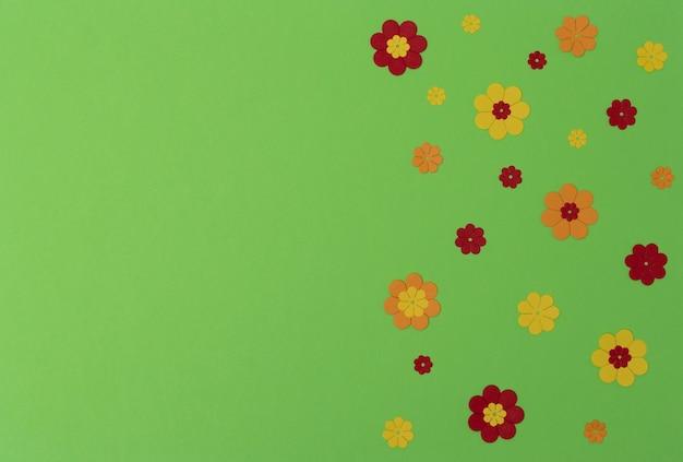 Flores de papel vermelho, amarelo e laranja brilhante em fundo verde com espaço de cópia