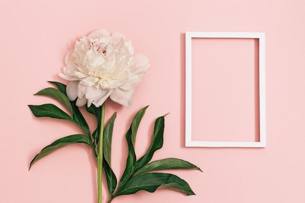 Flores de peônia branca com folhas em pastelpink e moldura quadrada branca
