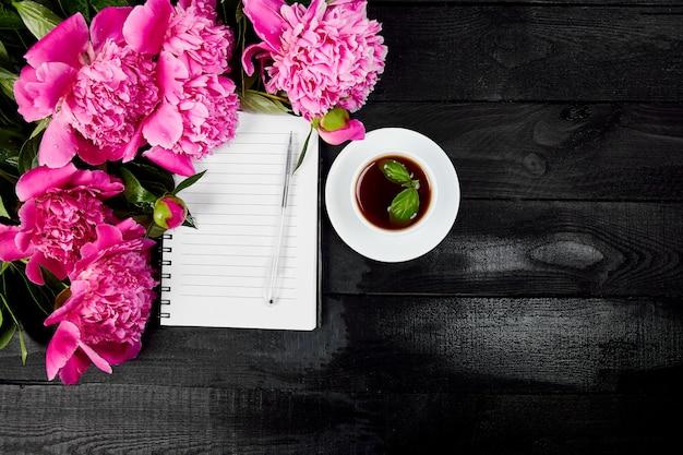 Flores de peônia em fundo preto com nota ou diário um
