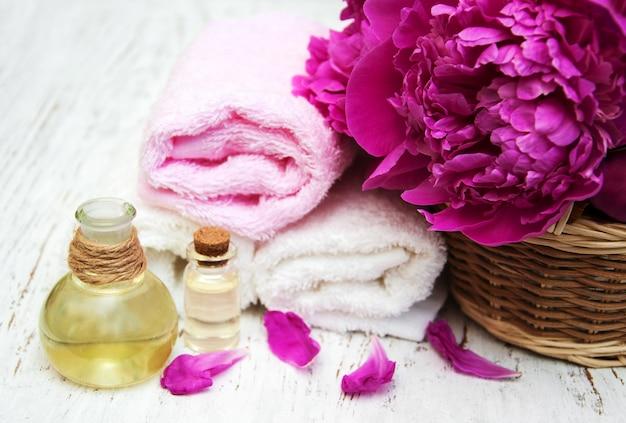 Flores de peônia, óleos de massagem e toalhas