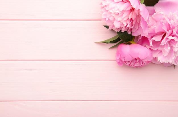 Flores de peônia purpura em madeira rosa.
