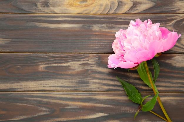 Flores de peônia rosa em madeira marrom.