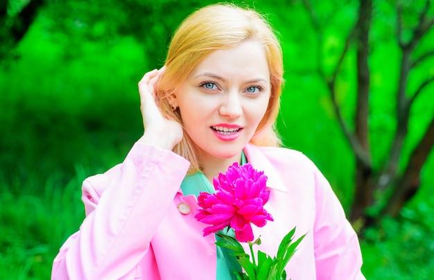 Flores de peônia, tempo de primavera, menina bonita com flor, mulher romântica com flor rosa no parque.