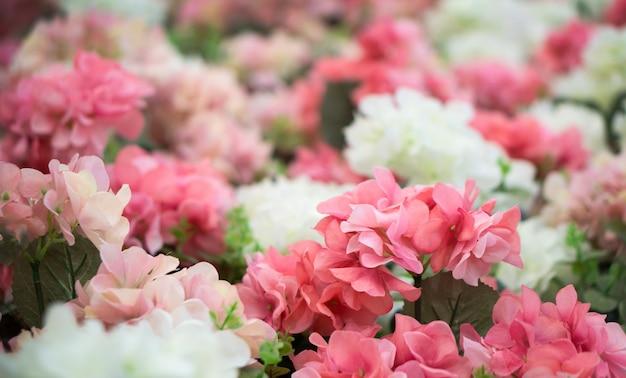 Flores de plástico rosa e brancas.