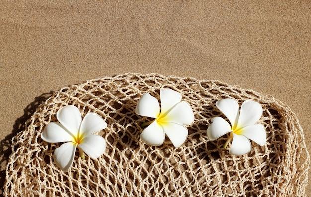 Flores de plumeria na bolsa de malha de praia na areia.