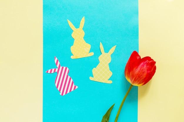 Flores de primavera, tulipas, coelhinho da páscoa em um fundo azul e amarelo.
