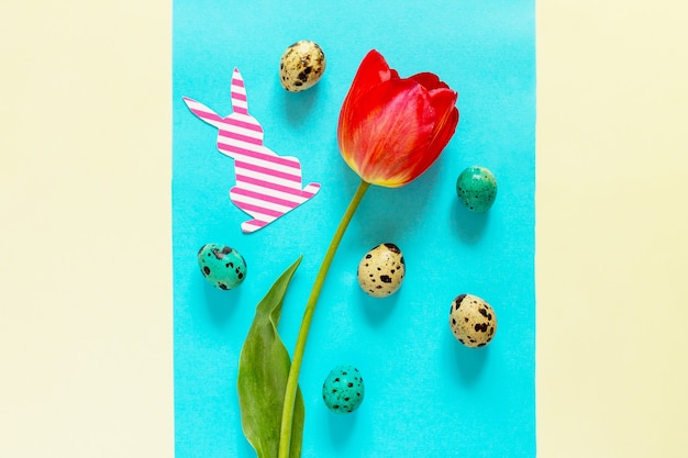 Flores de primavera, tulipas, coelhinho de ovos de páscoa em um fundo azul e amarelo. conceito mínimo de páscoa